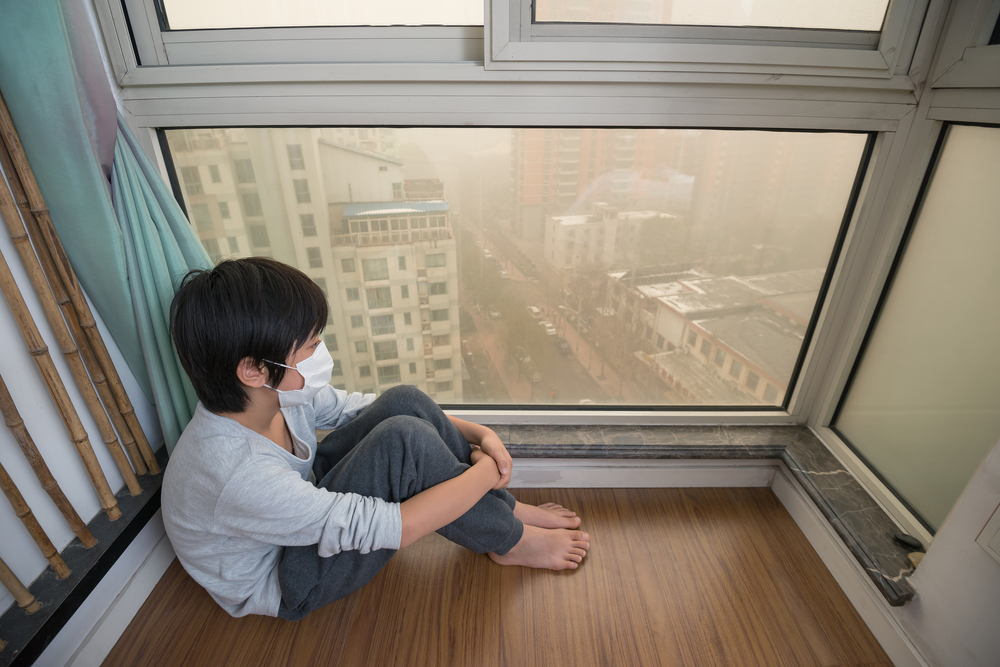 A boy wears an air mask and looks out of his window to a polluted day. Air pollution awareness grew in 2016, and Blueair hopes people will look for solutions this year.