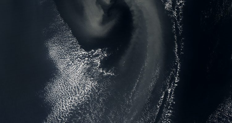 The image captures a swirling vortex of clouds and dust moving over the Arabian Sea. The counterclockwise direction is caused by the rotation of the Earth.