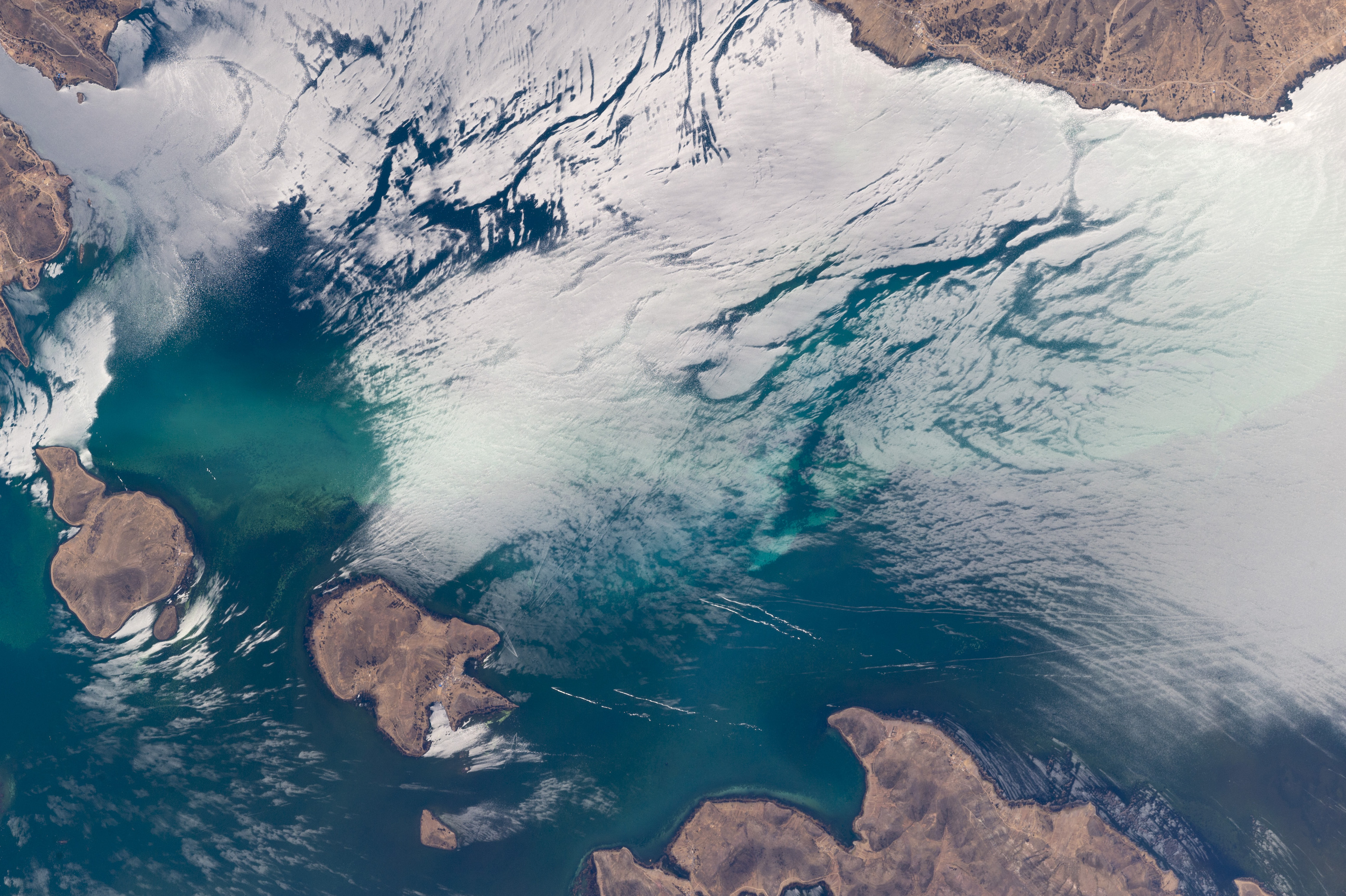 Today's Image of the Day comes thanks to the NASA Earth Observatory and features a look at sunglint on Lake Titicaca in the Andes Mountains.