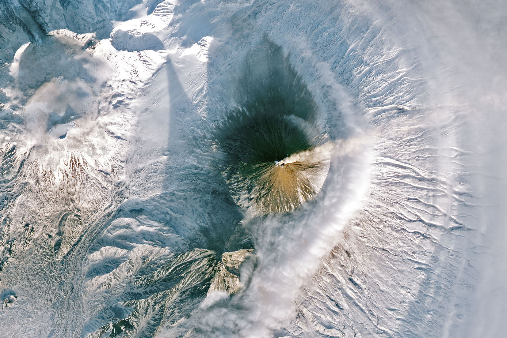Today's Image of the Day comes from NASA and features a look at plumes puffing out of the Klyuchevskaya volcano on the Kamchatka Peninsula.