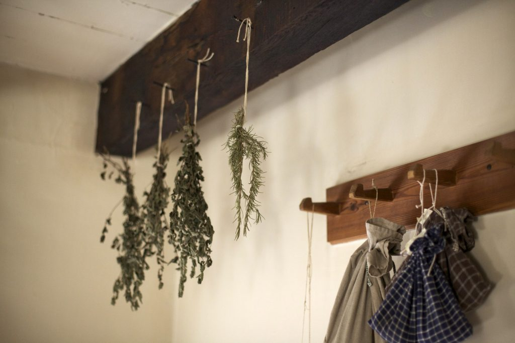 Herbs air drying in bundles haning from a ceiling beam with a coat rack in the lower right.