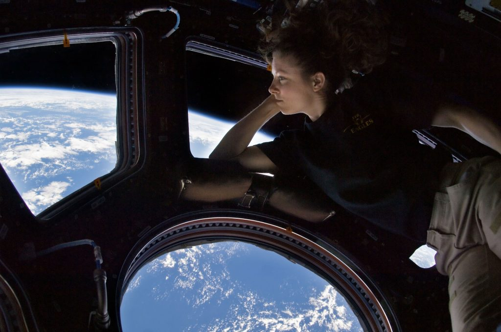 The view of earth from the international space station with an astronaut looking out the window.