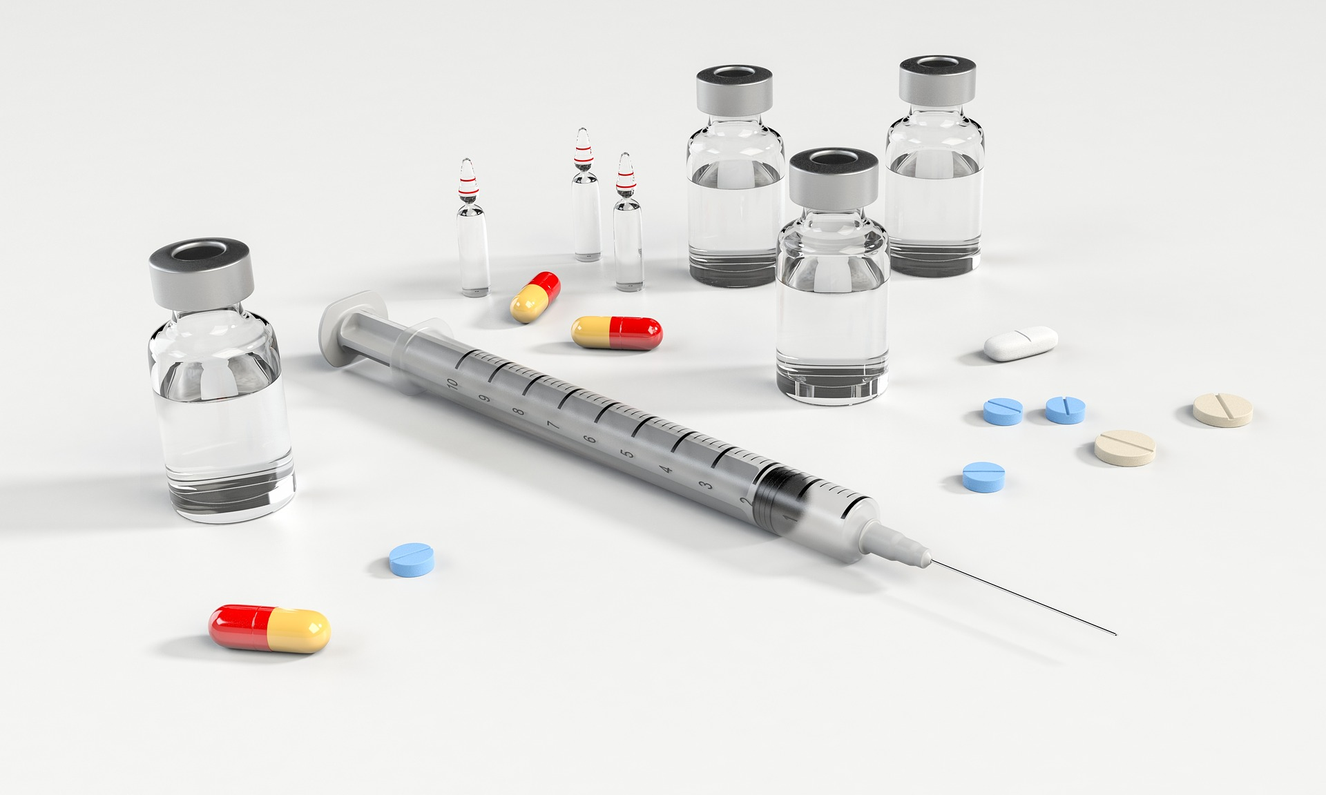 Pills, a syringe, ampules and viles of medicine on a white background.