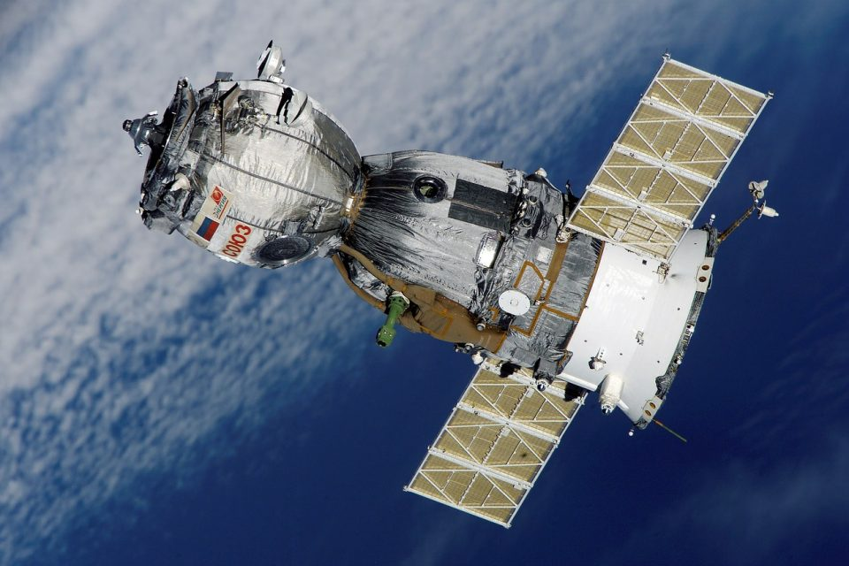 A Russian soyuz satellite orbiting over earth, see with clouds in the background.
